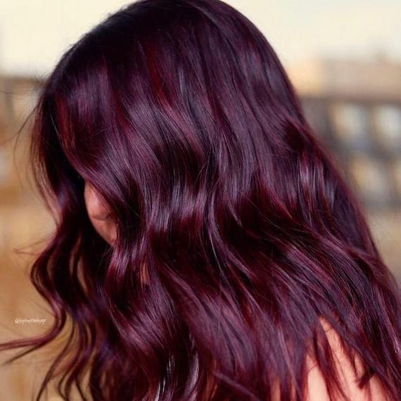 Side profile of woman with glossy, wavy, dark plum hair, created using Wella Professionals.