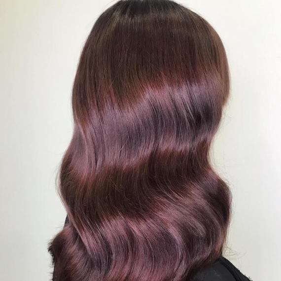 Back of woman's head with glossy, wavy, plum brown hair, created using Wella Professionals.