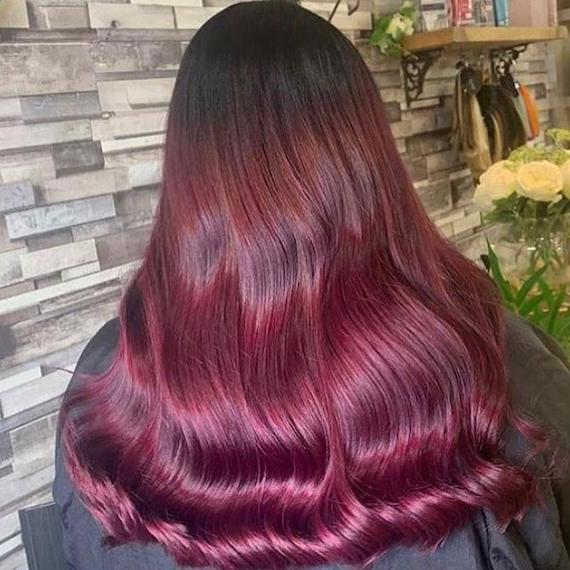 Back of woman's head with plum roots and raspberry mid-lengths, created using Wella Professionals.