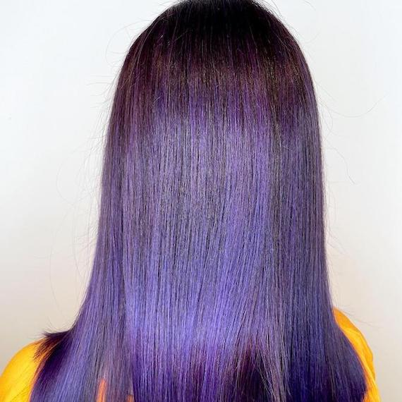 Back of woman's head with straight, shiny, purple hair, created using Wella Professionals.
