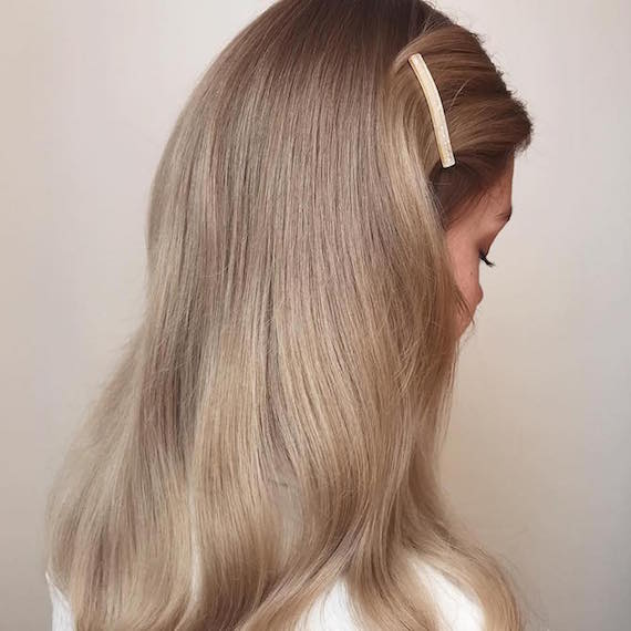 Side profile of woman with glossy blonde hair, created using Wella Professionals.