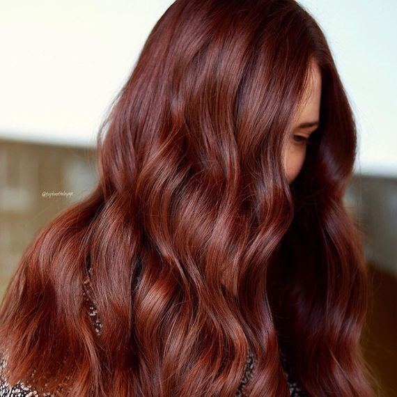 Side profile of woman with long, wavy, mahogany red brown hair, created using Wel-la Professionals.
