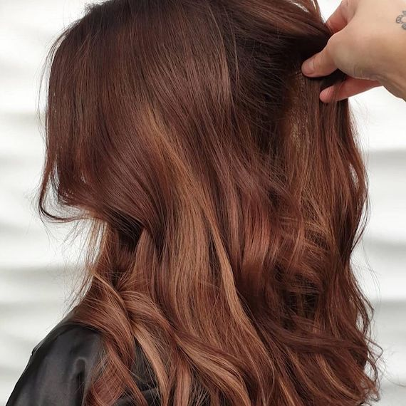 Side profile of woman with long, wavy, auburn red brown hair, created using Wella Professionals.