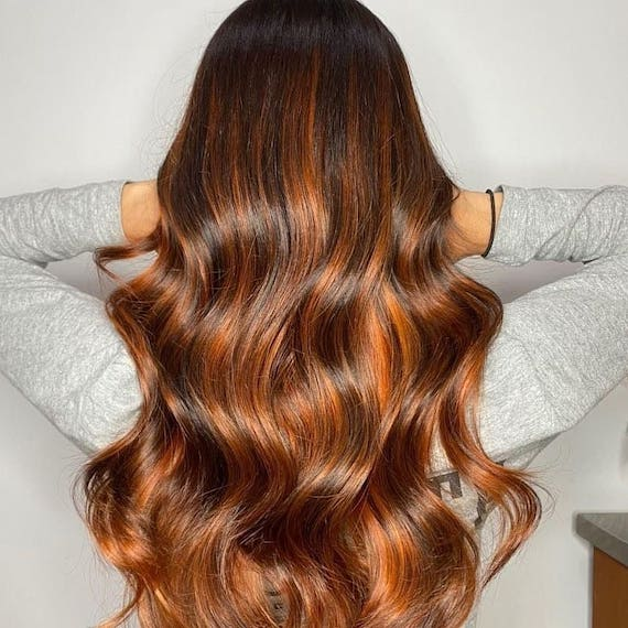 Back of woman's head with long hair and red brown balayage, created using Wella Professionals.