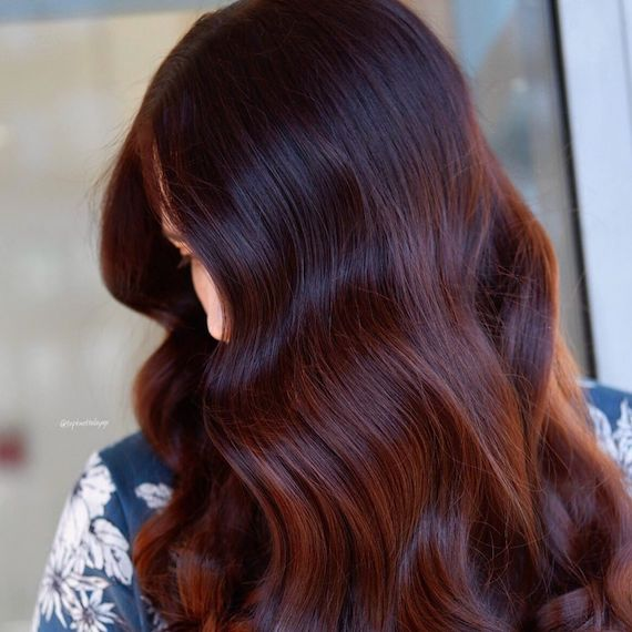 Side profile of woman with long, wavy, dark red brown hair, created using Wella Pro-fessionals.