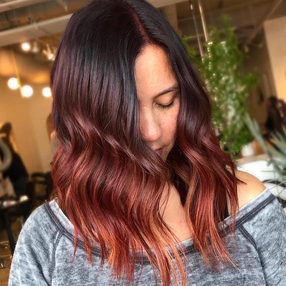Photo of woman with wavy long bob and dark red ombre hair color, created using Wella Professionals.