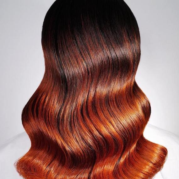 Back of woman's head with glossy, polished waves and red ombre hair color, created using Wella Professionals.