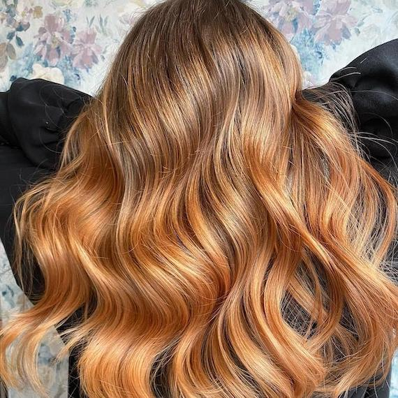 Back of woman's head with strawberry blonde ombre hair, created using Wella Professionals.
