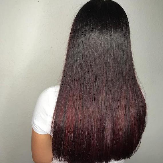 Back of woman's head with black and red ombre hair, created using Wella Professionals.
