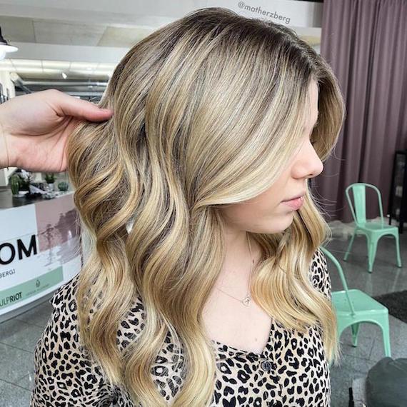 Hand tousling wavy, blonde hair in Wella Professionals salon.