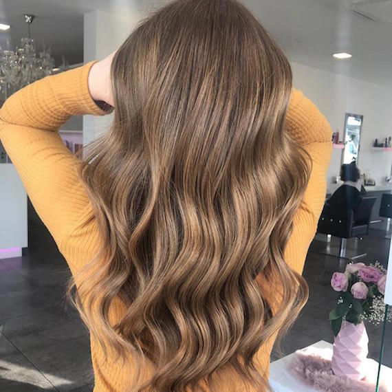 Photo showing back of woman's head as she swishes long, brown wavy hair in a Wella Professionals salon.