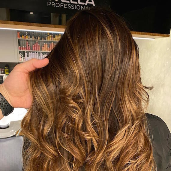 Hand tousling wavy, brown hair in Wella Professionals salon.