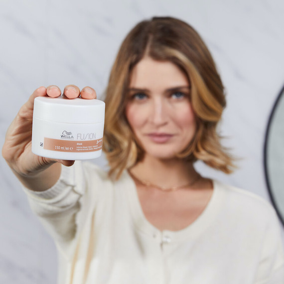 Woman with short hair holding up the Wella Fusion Intense Repair Mask.