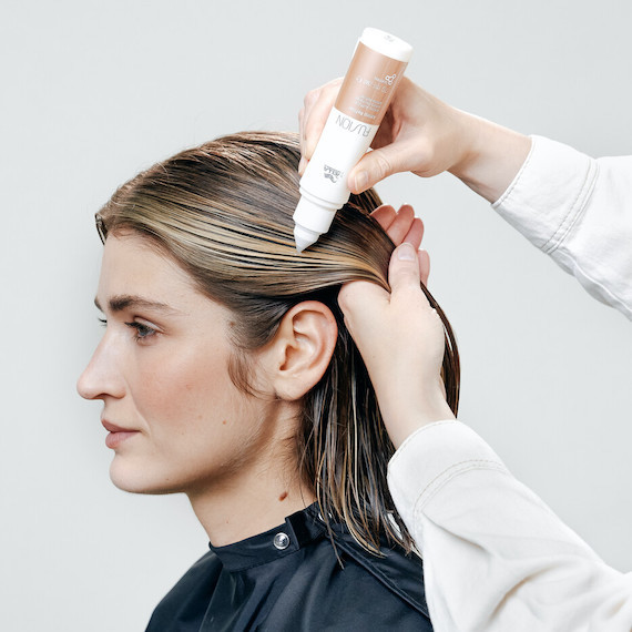 The Wella Fusion Amino Refiller is applied to a woman's hair.