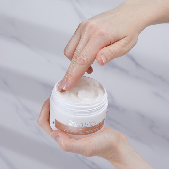 Hand dipping into the Wella Fusion Intense Repair Mask.