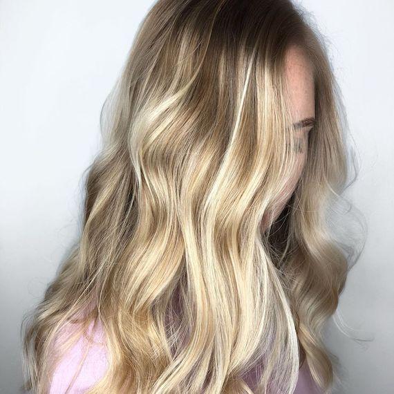 Frau mit langem, blondem Balayage und dunklem Haaransatz, kreiert mit Wella Professionals.