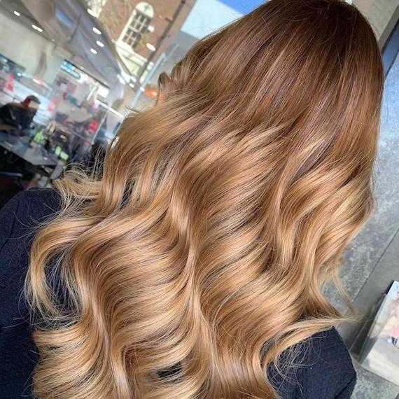 Frau mit blondbraunem Haar und einem dunklen Ansatz, kreiert mit Wella Professionals.