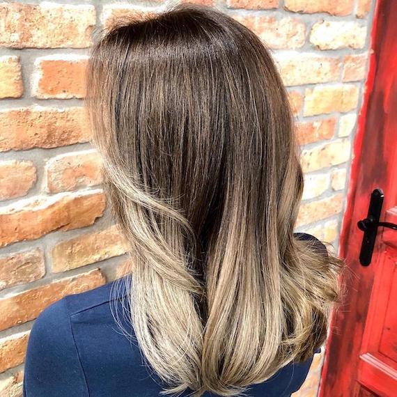 Frau mit aschblondem Ombré und dunklem Haaransatz, kreiert mit Wella Professionals.
