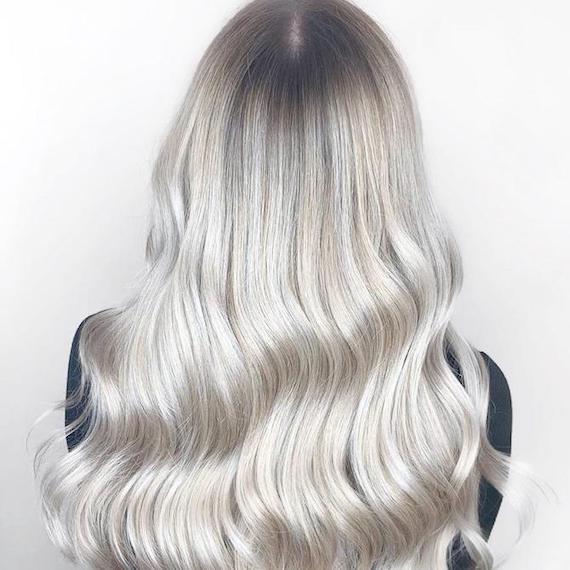 Frau mit eisblondem Haar und dunklem Ansatz, kreiert mit Wella Professionals.