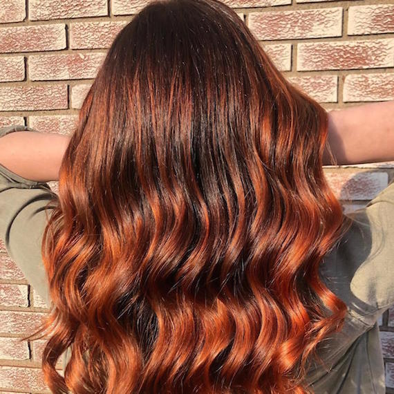 Back of woman's head with long, wavy, copper red hair and a shadow root, created using Wella Professionals.