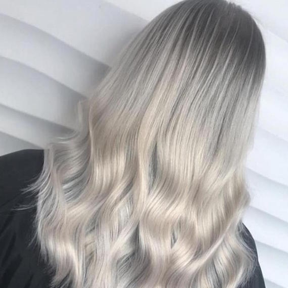 Back of woman's head with long, wavy, ice blonde hair and a shadow root, created using Wella Professionals.