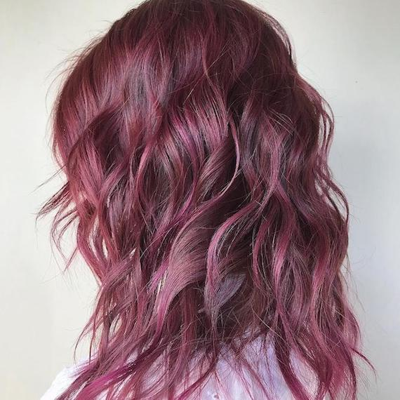 Side profile photo of woman with wavy, rose brown hair, created using Wella Professionals