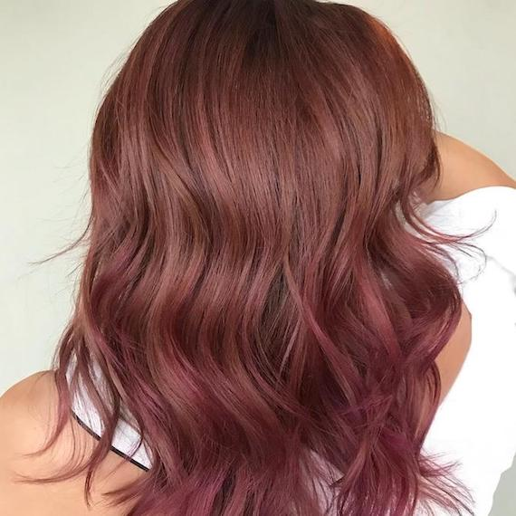 Back of woman's head showing mid-length, wavy hair with pink tones through the ends, created using Wella Professionals