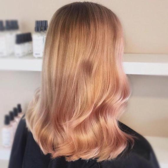 Back of woman's head showing long, wavy blonde hair with rose gold highlights, created using Wella Professionals.