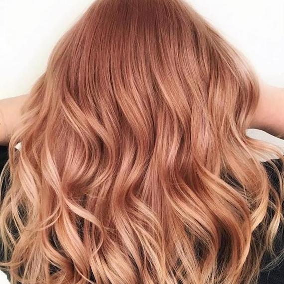 Back of woman's head showing long, wavy rose gold hair, created using Wella Professionals.