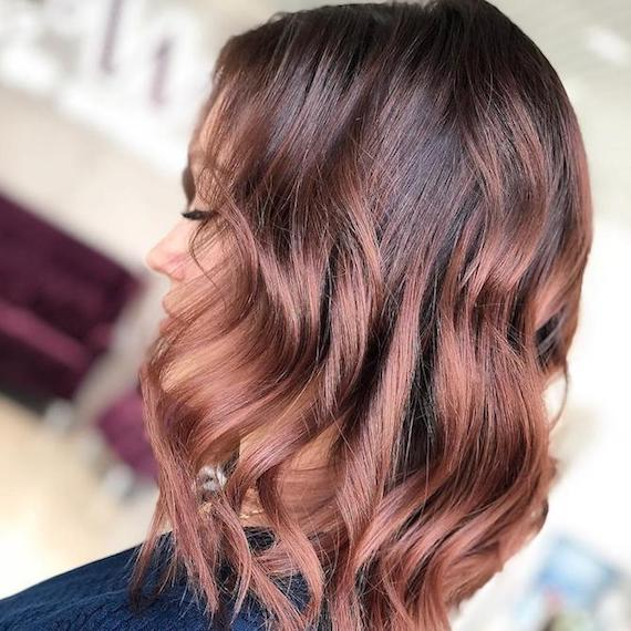 Side profile of woman with should-length, wavy rose brown hair, created using Wella Professionals.