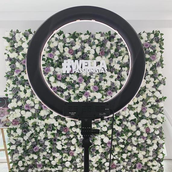 Photography ring light shown against a flower wall backdrop at a Wella Professionals event.