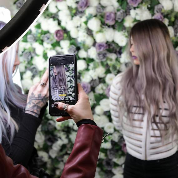 Woman posing against flower wall as she has her photo taken at a Wella Professionals event.