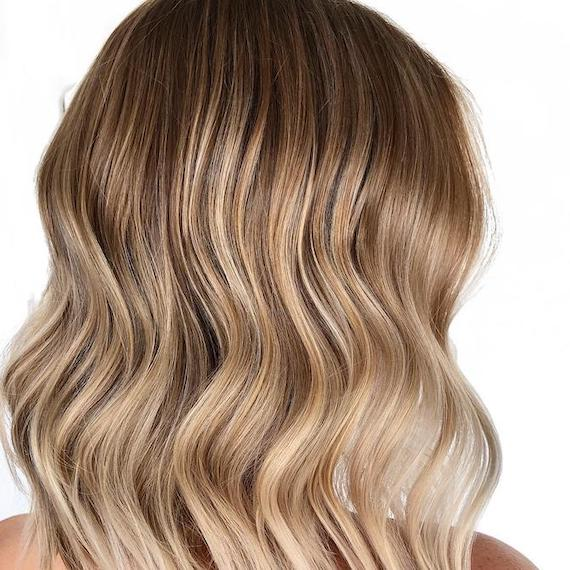 Side profile photo of woman with sandy blonde ombre hair, created using Wella Professionals.