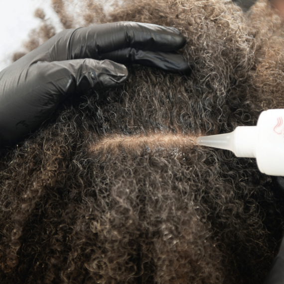 A close-up of Wella Professionals' Marula Oil Blend Scalp Primer being applied to a woman's scalp.
