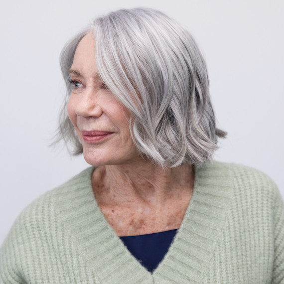Woman with short, grey bob haircut hair looks off to the side.