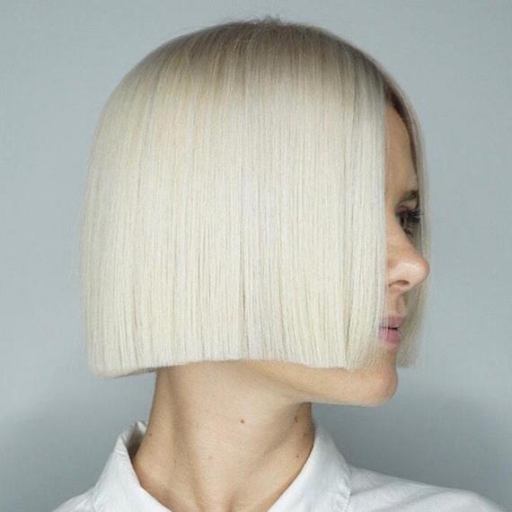 Side profile of woman with short platinum blonde hair, created using Wella Professionals.