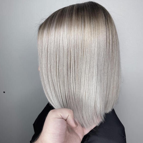Side profile of woman with ice blonde bob, created using Wella Professionals.