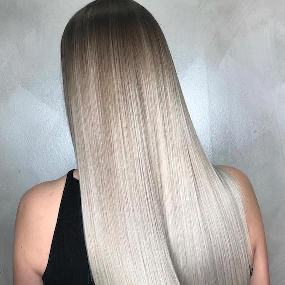 Back of woman's head with long, straight, silver ombre hair, created using Wella Professionals.