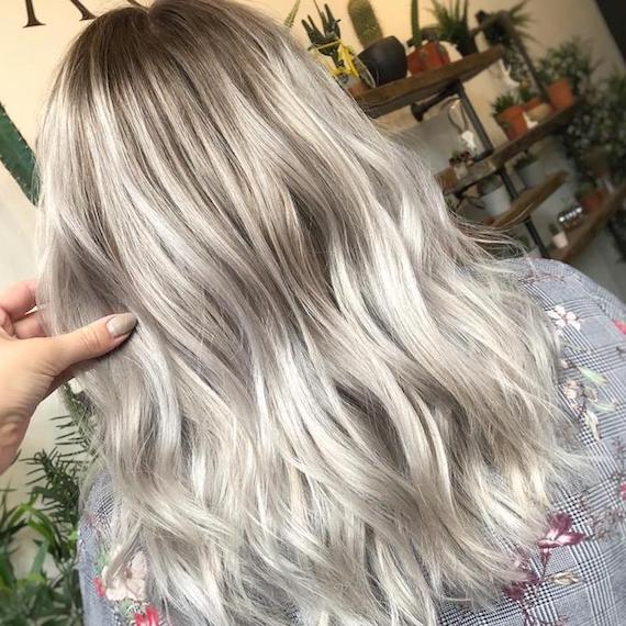 Back of woman's head with mid-length, tousled, silver balayage hair, created using Wella Professionals.