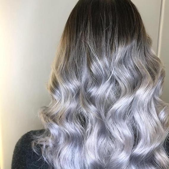 Back of woman's head with long, curly, silver grey balayage, created using Wella Professionals.