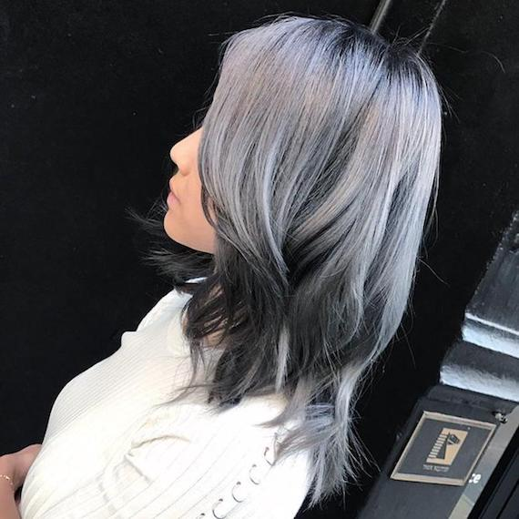 Side profile of woman with wavy, silver reverse balayage, created using Wella Professionals.