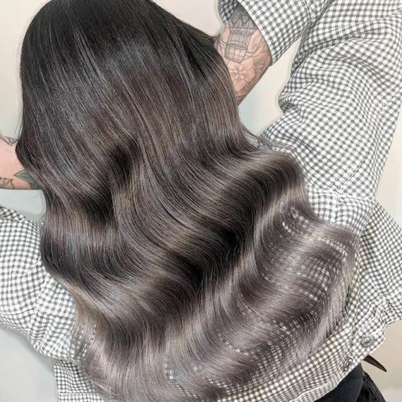 Back of woman's head with long, wavy, dark silver balayage hair, created using Wella Professionals.