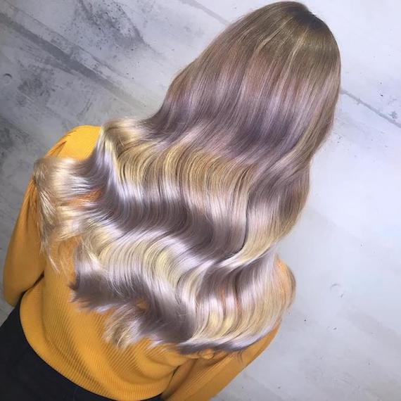 Back of woman's head with long, wavy, pale balayage hair, created using Wella Professionals.