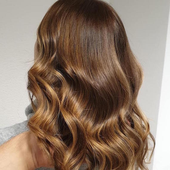 Back of woman's head with wavy, light brown sombre hair, created using Wella Professionals.