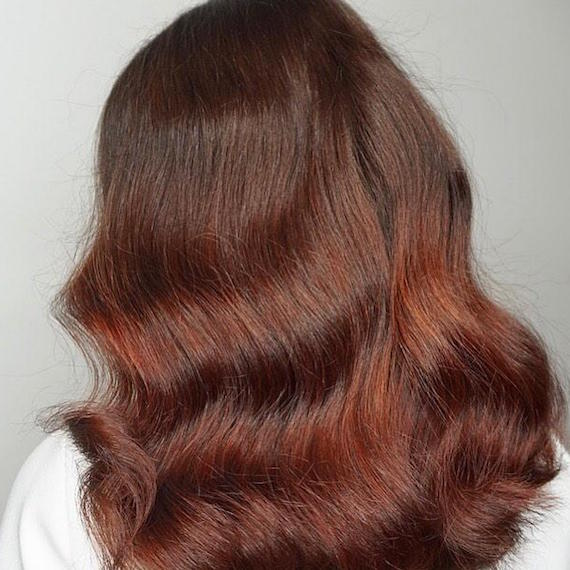 Back of woman's head with loosely curly, burgundy sombre hair, created using Wella Professionals.