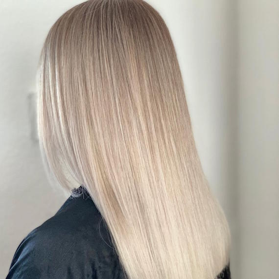 Side profile of woman with super-straight, ice blonde sombre hair, created using Wella Professionals.
