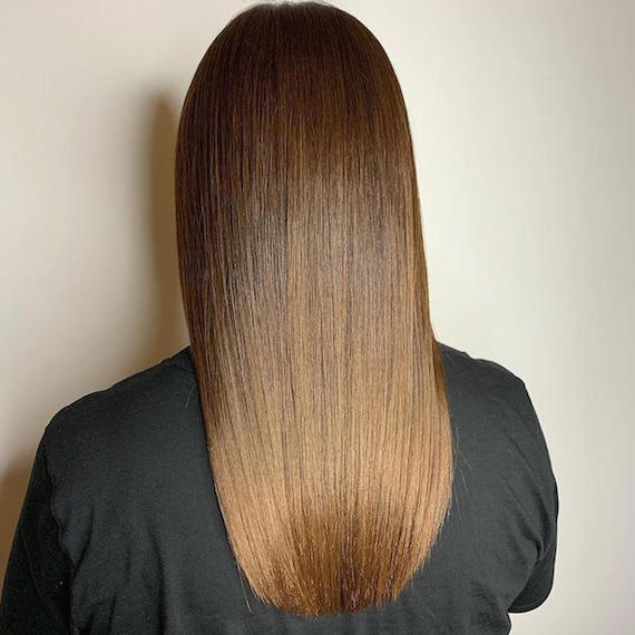 Back of woman's head with long, straight, brown sombre hair, created using Wella Professionals.