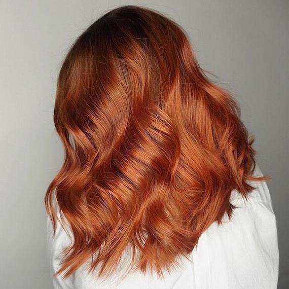 Side profile of woman with glossy, wavy, red sombre hair, created using Wella Professionals.