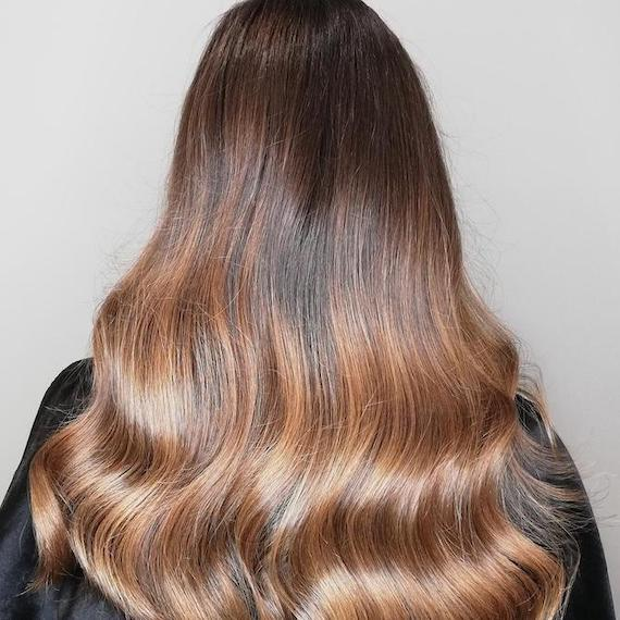 Back of woman's head with long, wavy, honey brown hair, created using Wella Professionals.