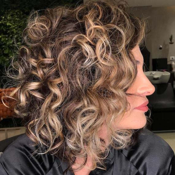 Side profile of woman with curly hair and blonde highlghts, created using Wella Professionals.